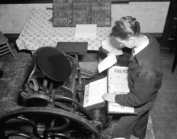 1930s black and white image of a man using a printing press.